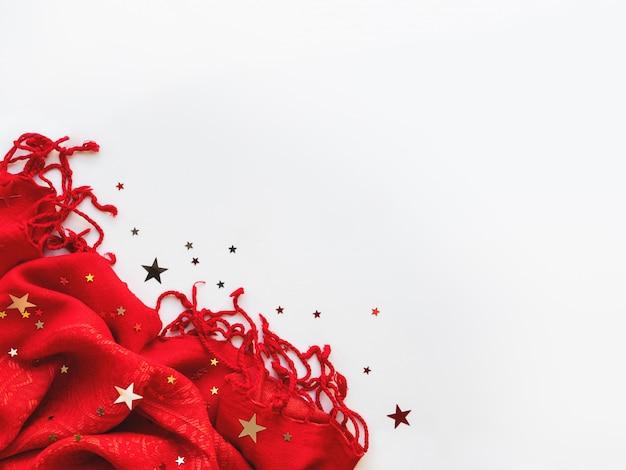 白地に銀と金色の星の紙吹雪と明るい赤いスカーフ。 copyspaceで折り畳まれた暖かいアクセサリー。