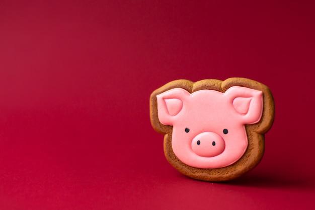 赤いcopyspaceにかわいいピンクのブタのジンジャーブレッドクッキー