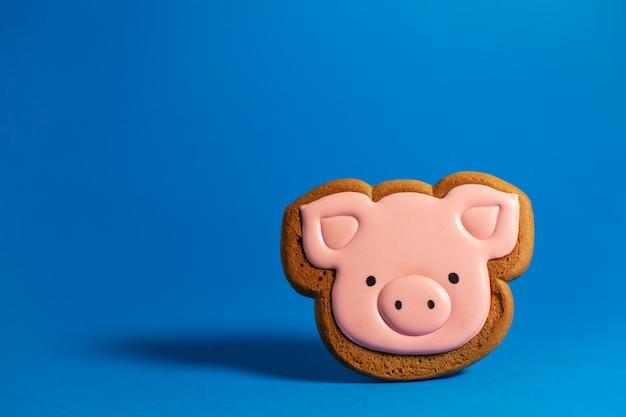 Печенье пряника милой розовой свиньи на сини. традиционная рождественская еда. рождество и новогодний праздник. copyspace
