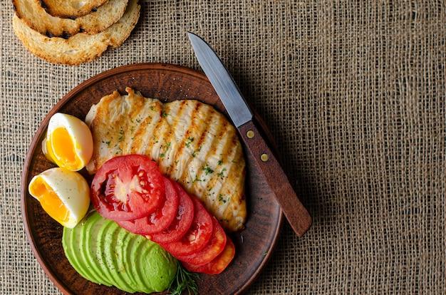 Здоровая пища жареная куриная грудка с авокадо, помидорами, тостами и яйцом всмятку. плоская планировка, copyspace