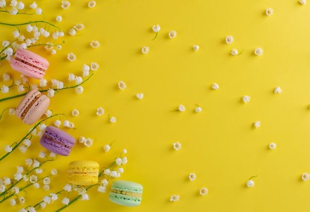 カラフルなマカロンまたはマカロンは、黄色の谷の咲くユリの花で飾られています。甘いフランスのデザートのコンセプトです。フレーム構成平らに置きます。 copyspace