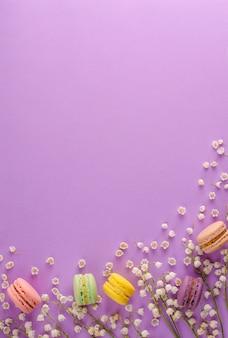 カラフルなマカロンは、紫色の背景に咲く谷のユリで飾られました。甘いフランスのデザートのコンセプトです。フレーム構成平らに置きます。 copyspace垂直。グリーティングカードの概念