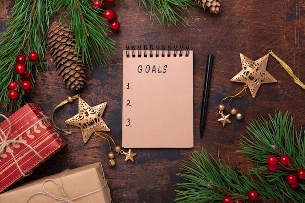 モミの枝、ギフト、木製の背景にノート。新しい目標。クリスマスの背景。トップビュー、copyspace。