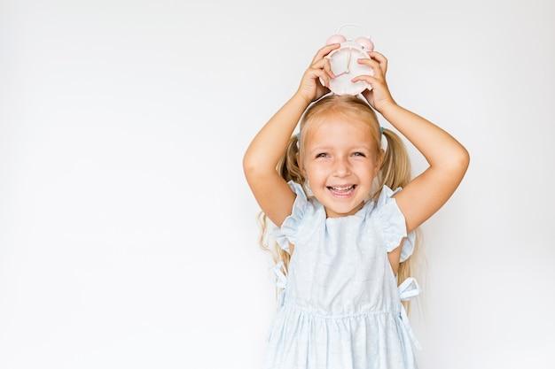 Милая маленькая девочка держит будильник на белом с copyspace
