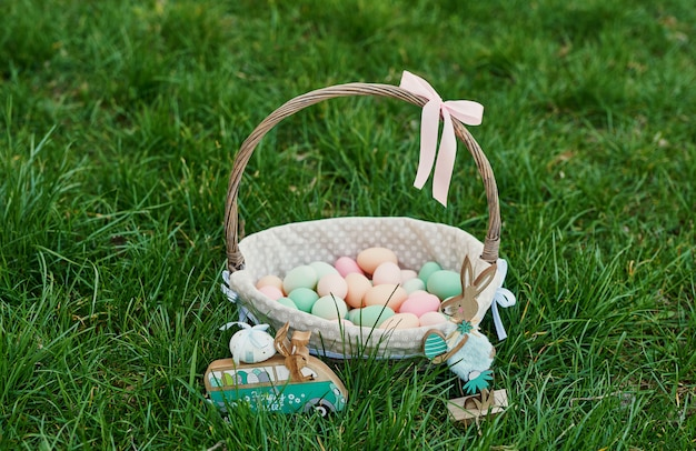 Пасхальная корзинка на зеленой траве весной. симпатичное яйцо охота за пасхальными яйцами. счастливой пасхи открытка с copyspace. шаблон поздравительной открытки пасхи. яичка на траве. концепция праздника весны с космосом экземпляра