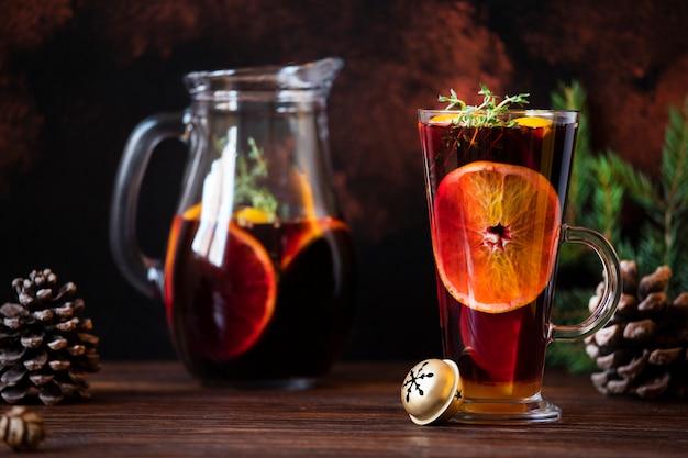グリューワインクリスマスの装飾が施された木製のテーブルに赤ワイン、柑橘類、スパイスで作られた温かい飲み物。グリューワインとガラスとデカンター。暗い背景。クローズアップ、カラフル、copyspace