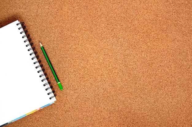 スパイラルノートとシンプルな緑色の鉛筆。背景copyspaceのトップビュー。学校のコンセプトに戻る