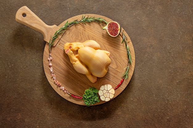 Рождественская курица перед приготовлением. кукурузная курица на круглой разделочной деревянной доске готова к приготовлению с розовой гималайской солью, розмариновым чесноком, острым перцем и инжиром. крупный план. вид сверху. copyspace.