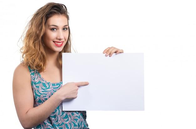 Счастливая усмехаясь молодая женщина показывая пустой пустой шильдик с copyspace