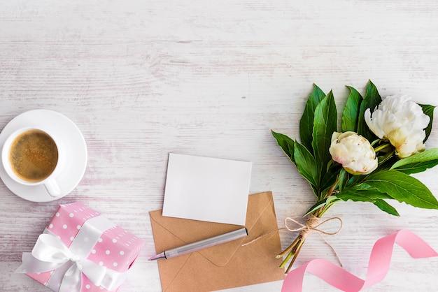 白紙の素朴なcopyspace上の空白のメモ、クラフト封筒、コーヒーカップ、牡丹の花の平面図です。