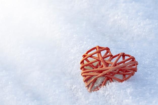 Красное заплетенное сердце на белом снегу. блики от солнца. символ любви и теплых и холодных отношений copyspace