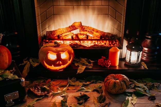 暖炉の近くの不気味なハロウィーンカボチャ。背景に火と乾燥した葉。ランタンのジャック、copyspace。暗闇で撮影します。