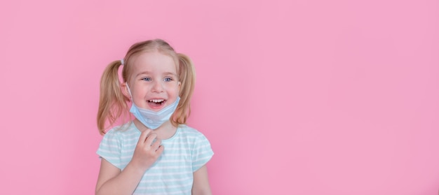 楽観的、笑顔の幸せな少女は、パンデミアの終わりを示すピンク色のスペースで顔から医療用マスクを脱いでいます。 copyspace。