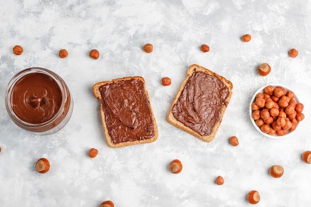 Шоколадный спред или нуга крем с лесными орехами в стеклянной банке на бетоне, copyspace