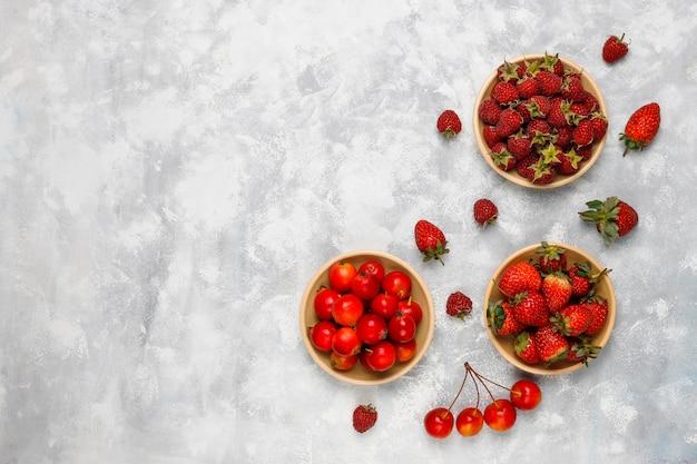Свежие органические ягоды на сером бетоне, вид сверху, copyspace