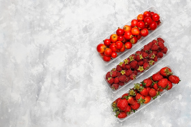 Свежие органические ягоды в пластиковых коробках на сером бетоне, вид сверху, copyspace