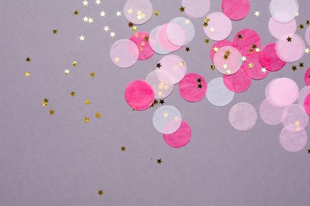 Розовый конфетти с золотыми звездами на сером с copyspace