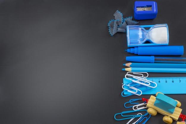 教育または学校に戻る。 copyspaceと黒板に青い学校用品。