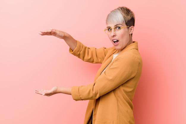 カジュアルなビジネス服を着た若い白人女性はショックを受け、手の間にcopyspaceを持って驚いた。