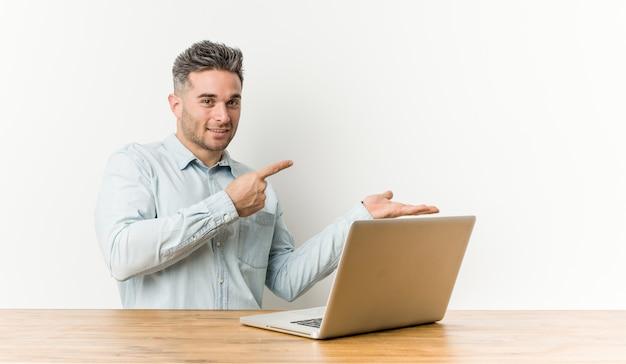 Молодой красавец, работающих с его ноутбук возбужденных, держа copyspace ладони.