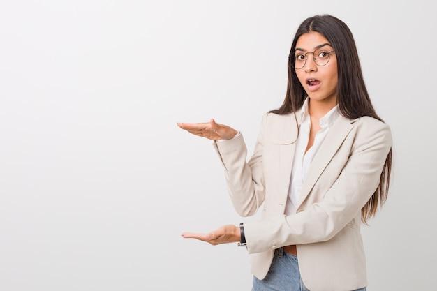 手に対してcopyspaceを保持しているショックを受けて驚いた白に対して分離された若いビジネスアラブ女性。