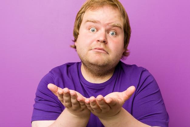 Молодой подлинный рыжий толстяк впечатлен, держа copyspace ладони.