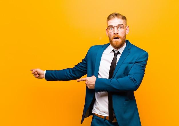 驚いた、口を開けた外観のオレンジ色の側のcopyspaceを指しているショックと驚きを感じて若い赤い頭の実業家