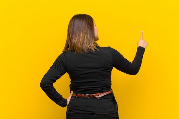 Женщина парикмахера стоя и указывая к объекту на copyspace, оранжевом вид сзади