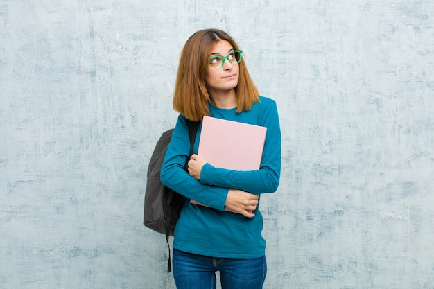 Молодой студент женщина с озабоченным, растерянным, невежественным выражением, глядя на copyspace, сомневаясь против гранж стены