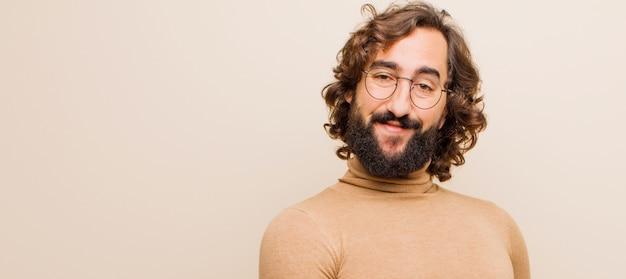 若いひげを生やした狂気の男元気に笑顔、幸せを感じて、フラットカラーに対して手のひらでcopyspaceを表示