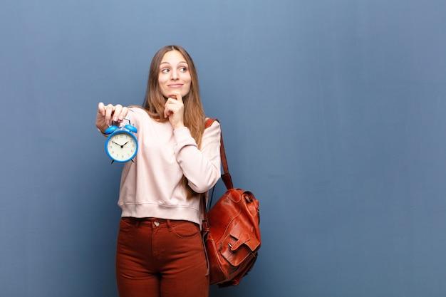 Молодая милая женщина с будильником против сини с copyspace