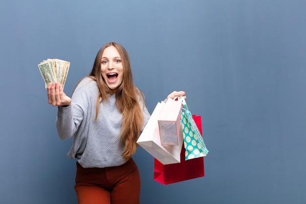 Copyspaceと青に対して買い物袋を持つ若いきれいな女性