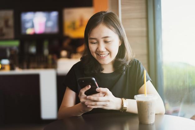 アジア民族の若い女性はリラックスしてコーヒーショップでアイスコーヒーを飲みます。カフェやレストランでコーヒーを飲みながらスマートフォンを使用してメッセージを送信する女性はcopyspaceでクローズアップ。