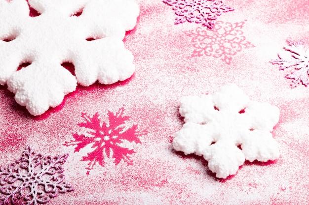 ピンクの背景にピンクと白の雪。クリスマスの背景。上面図。 copyspace。装飾的な雪。