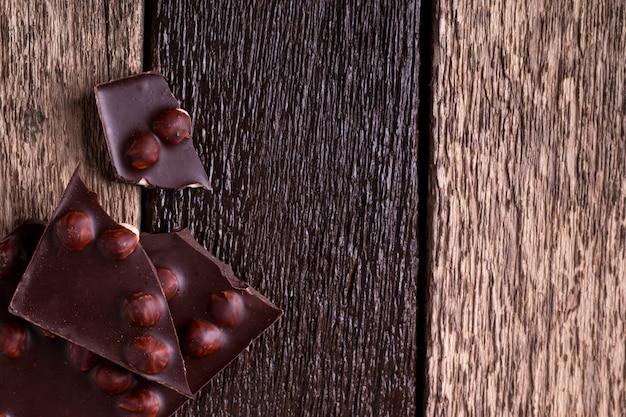 Части шоколада с фундуком на деревянном. вид сверху. copyspace.
