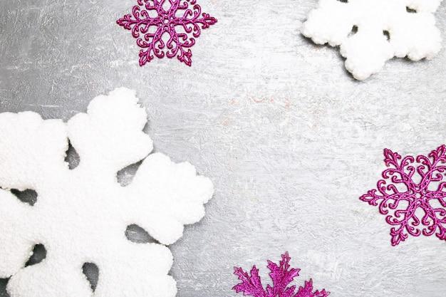 グレーに白とピンクの装飾的なスノーフレーク。クリスマスのグリーティングカード。 copyspace。上面図。