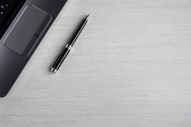 ノートパソコンとペンと白いオフィステーブル。 copyspaceとトップビューの背景。テーブルのワークスペース。仕事とオフィスのコンセプト