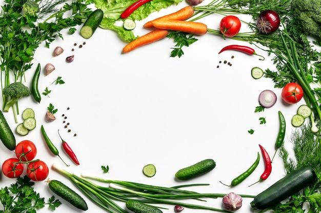 中央の背景にcopyspaceと野菜のフレーム。野菜、トマト、ズッキーニ、ブロッコリー、ニンジン、パセリ、玉ねぎ、キュウリのセット。新鮮な天然野菜