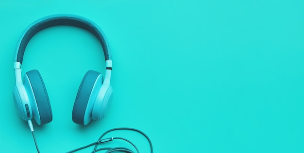 色付きの背景にターコイズブルーのヘッドフォン。 copyspaceの音楽コンセプト