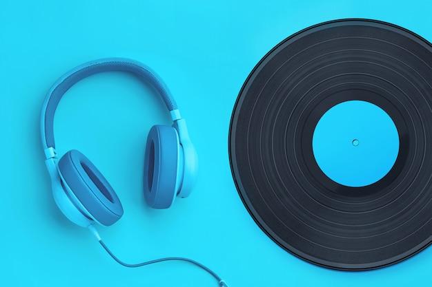 色付きの背景にビニールレコードとターコイズブルーのヘッドフォン。 copyspaceの音楽コンセプト。分離されたシアンの背景にヘッドフォン