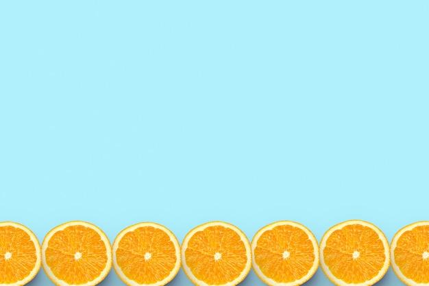 Красочные фрукты граница свежих апельсиновых дольок на цветном фоне с copyspace