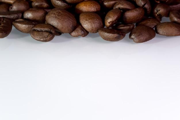 Жареные кофейные зерна на белом столе с copyspace