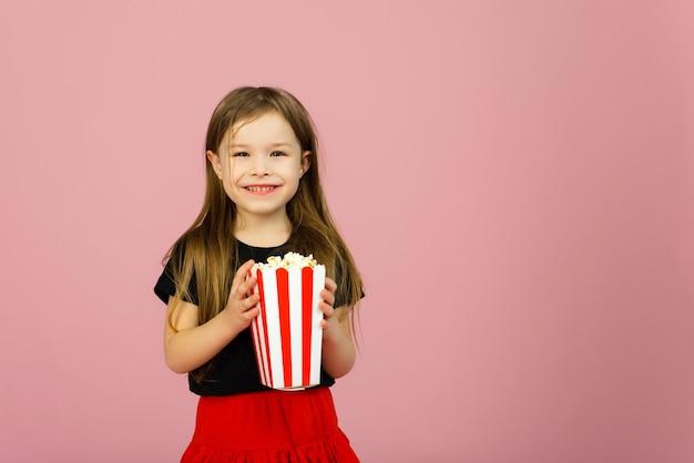 Счастливая милая маленькая девочка держит попкорн в руках. концепция просмотра кино в кинотеатре или дома. copyspace