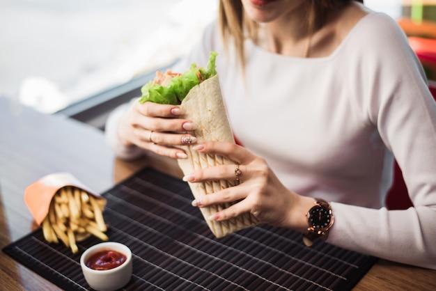 Шаурма в руках женщины. концепция быстрого питания. красивая женщина ест картофель фри и фахито в кафе быстрого питания. copyspace