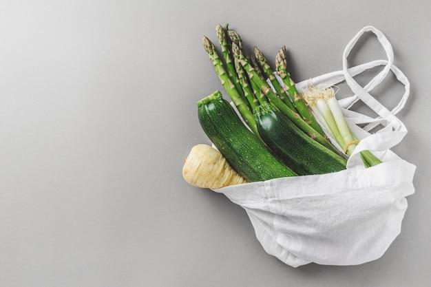 Различные овощи в текстильной сумке на сером copyspace