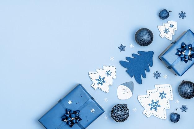 Новый год и рождество кадр. рождественские украшения подарочные коробки, звезды, елки, елочные шары, санта-клаус на синем. вид сверху, плоская планировка, copyspace. модный цвет года.