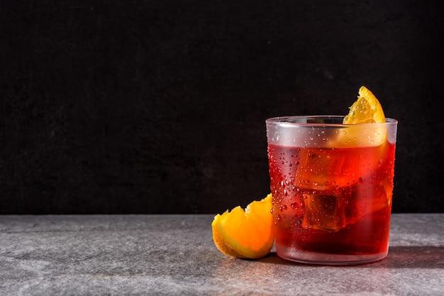 Негрони коктейль с кусочком апельсина в стакане на черном, copyspace