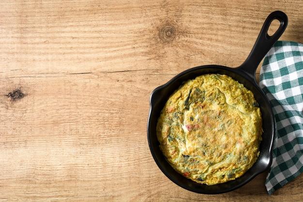 卵と野菜の鉄製の鍋、木製のテーブルで作られたフリッタータトップビューcopyspace