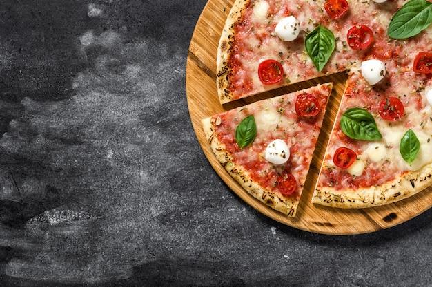 トマト、チーズ、バジルの黒い石の上でイタリアのピザのスライストップビューcopyspace