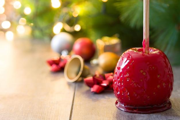 Конфеты рождественские яблоки и рождественские огни copyspace